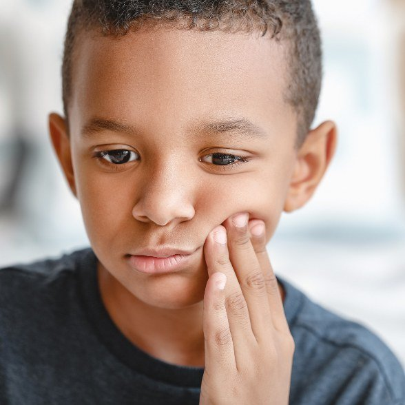 Child in need of emergency dentistry holding cheek in pain