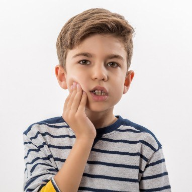 Little boy with toothache holding cheek