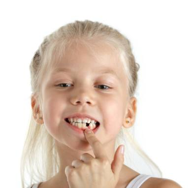 Little girl pointing to knocked out baby tooth