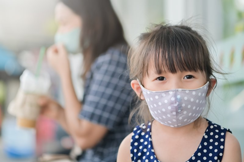 a little girl wearing a gray polka dot mask out in public