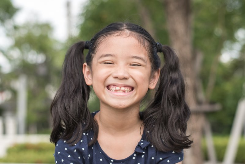 a little girl wearing her hair in pigtails and showing off her smile in Chesterfield
